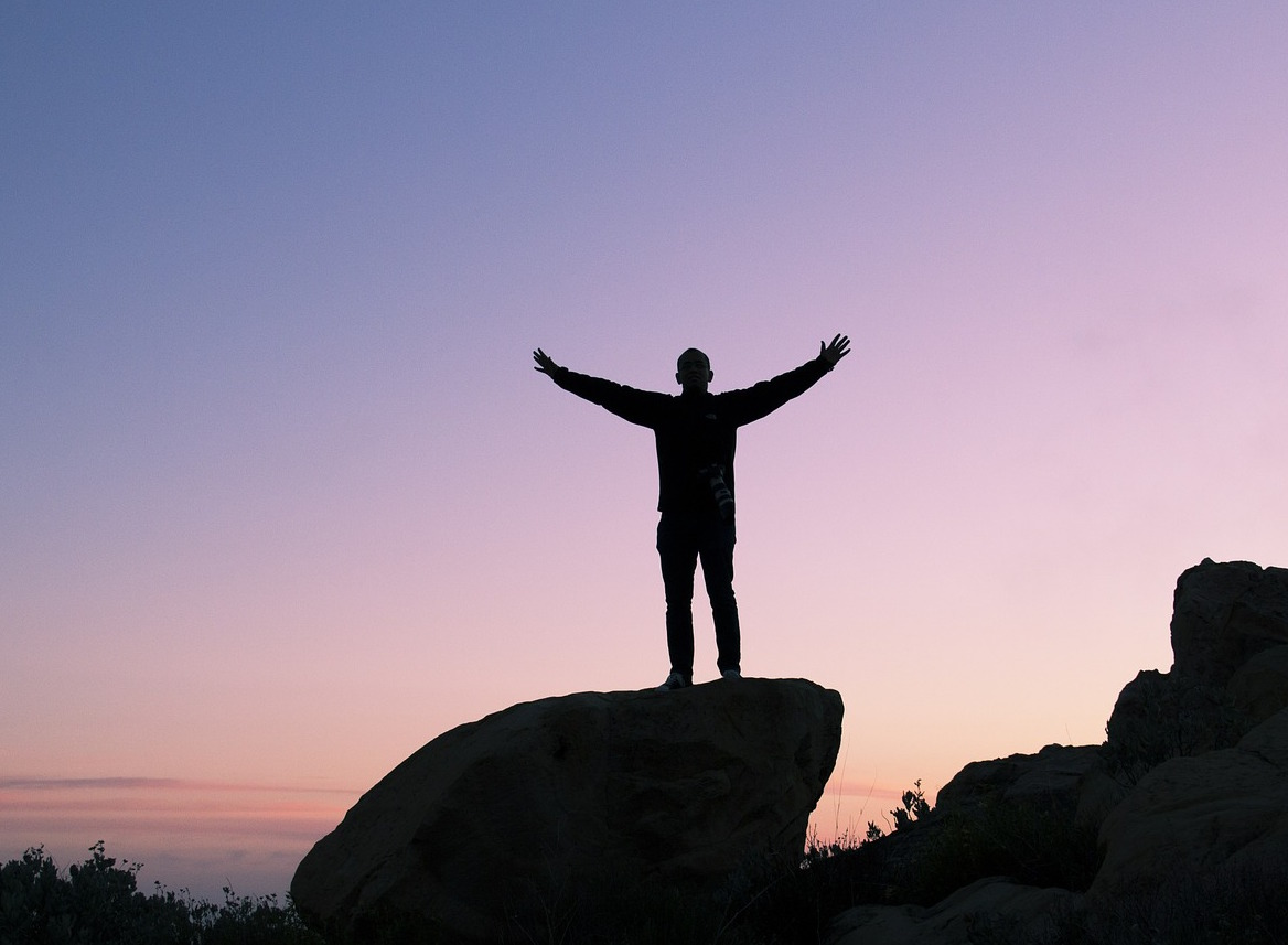 Silhouette of a man on a rock with arms spread wide, finally realising that failure is not the end, just a step nearer to success...