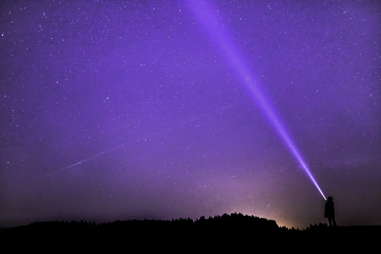 Man shining a light up to the stars - seeing how vast the Universe is and realizing that anything is possible...
